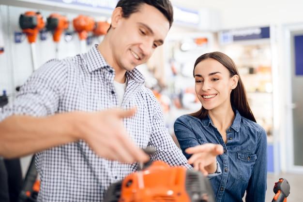 Vendeur dans le magasin montre aux clients un coupe-herbe.
