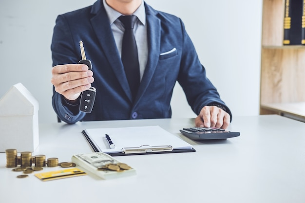 Vendeur détenant une clé et calculant le prix de la vente d'une nouvelle voiture et d'un prêt immobilier