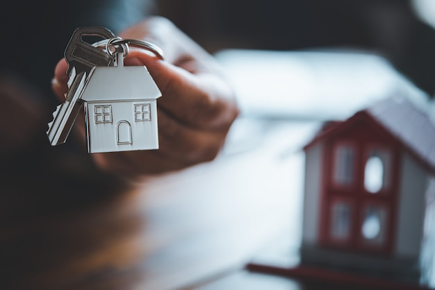 Vendeur détenant le concept de clés de maison, clés de maison pour nouvelle maison, achat d'une nouvelle maison