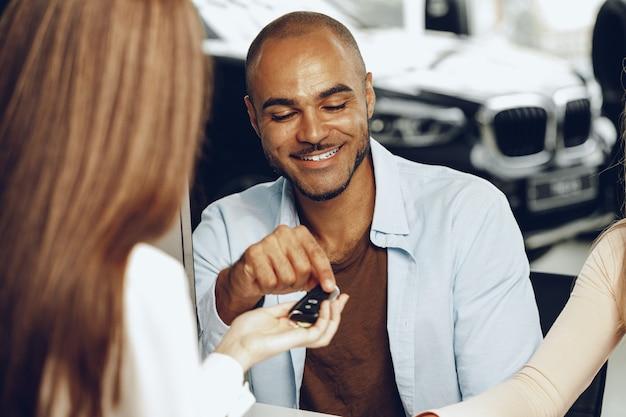 Vendeur donnant la clé à l'acheteur dans un salon de voiture