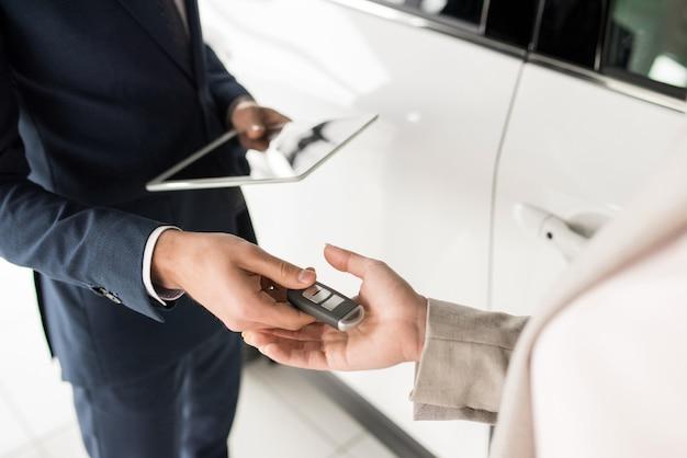 Vendeur donnant des clés de voiture au client