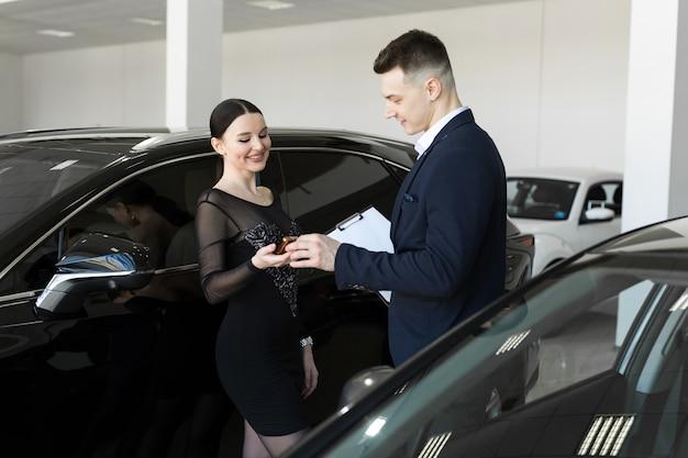 Le vendeur donne à l'acheteur les clés d'une nouvelle voiture dans la salle d'exposition