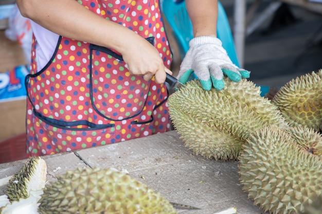 Le vendeur de durian épluche le durian pour le client sur le marché local des fruits