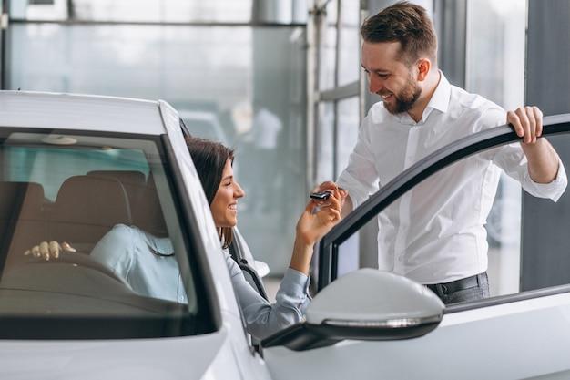 Vendeur et femme à la recherche d'une voiture dans une salle d'exposition