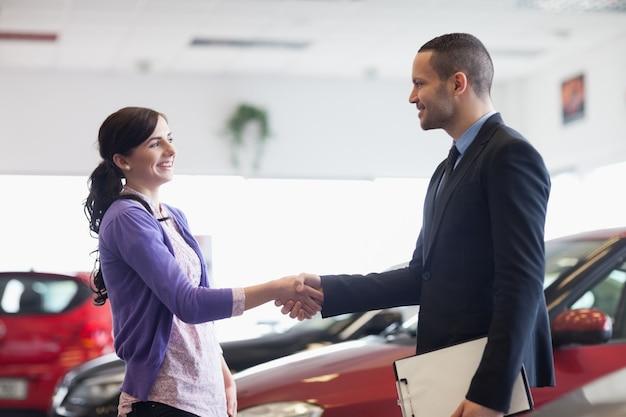 Vendeur et une femme se serrant la main