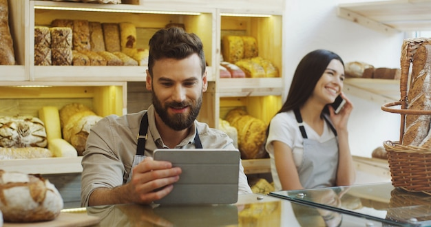 Vendeur d'un homme de race blanche à l'aide d'une tablette tout en se tenant au comptoir de la boulangerie, sa collègue de travail parlant au téléphone derrière lui. à l'intérieur