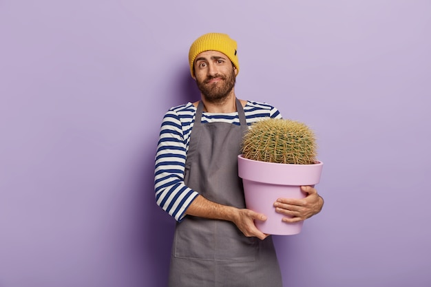 Vendeur inconscient pose dans un magasin de fleurs avec pot de cactus