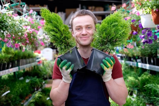 Vendeur de jeune homme en serre de marché aux plantes au travail