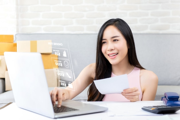 Vendeur en ligne jeune femme travaillant sur un ordinateur portable