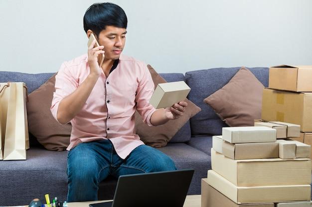 Vendeur en ligne masculin asiatique parlant au téléphone tout en tenant une boîte de son produit