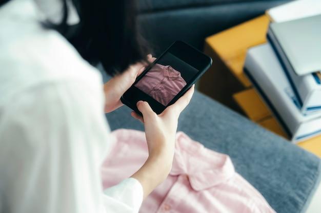 Le vendeur en ligne propriétaire prend une photo du produit pour le télécharger sur la boutique en ligne du site web.