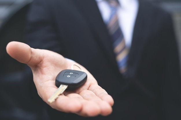 Le vendeur livre les nouvelles clés de voiture au client dans la salle d'exposition.