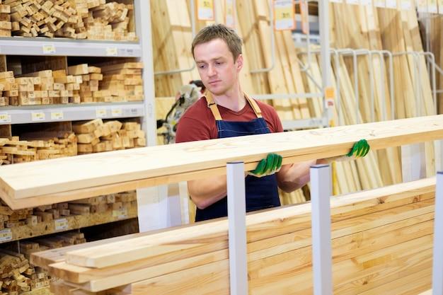 Vendeur en magasin de construction avec du bois