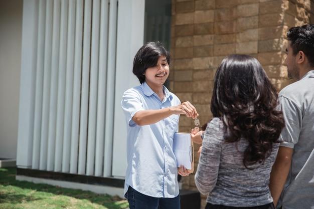 Vendeur de maison donnant la clé au nouveau propriétaire