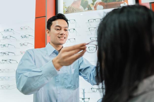 Un vendeur masculin sert et habille une cliente alors qu'elle est chez un opticien