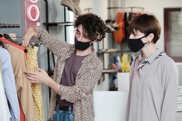 Vendeur en masque aidant la femme à choisir la nouvelle robe dans le centre commercial