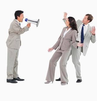 Vendeur avec mégaphone criant à des collègues