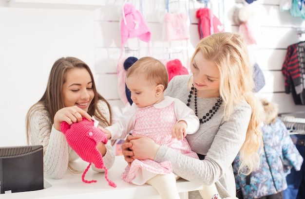 Le vendeur montre un chapeau rose d'hiver à une fille avec un pompon pour sélectionner les achats