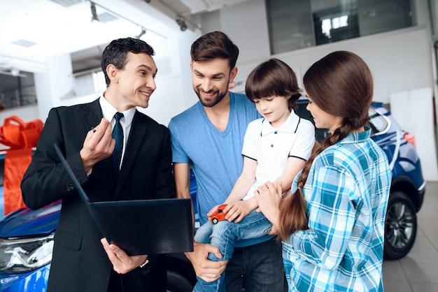 Le vendeur montre à la famille le choix des voitures.