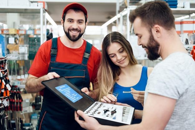 Le vendeur montre la nouvelle boîte à outils de quelques clients.