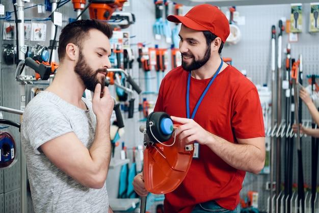 Un vendeur montre une nouvelle tondeuse à gazon à un client
