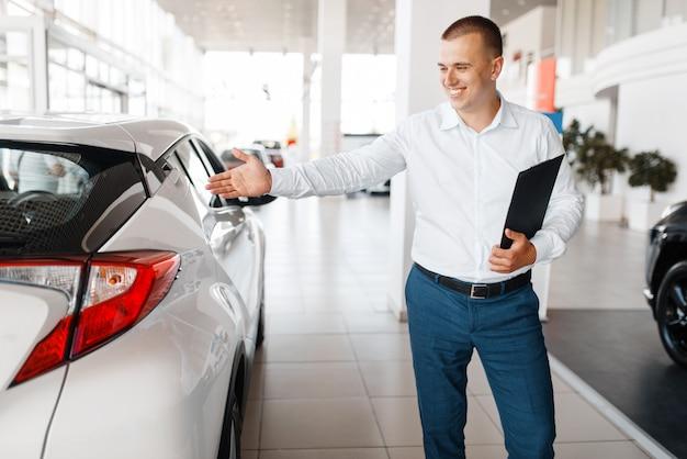 Le vendeur montre une nouvelle voiture dans la salle d'exposition. client masculin achetant un véhicule en concession, vente d'automobiles, achat d'automobiles