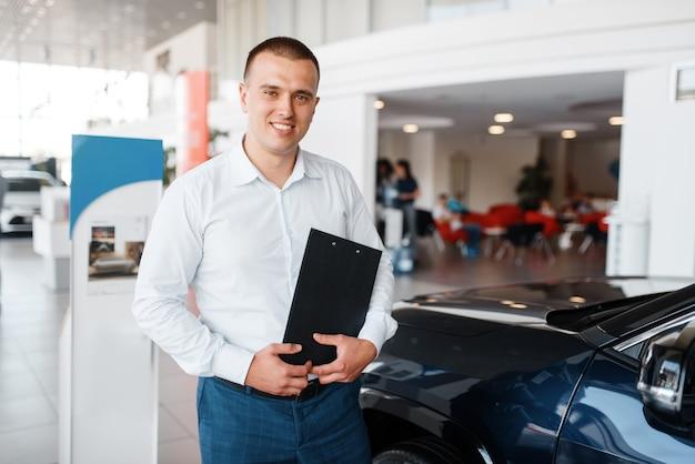 Le vendeur montre une nouvelle voiture dans la salle d'exposition.