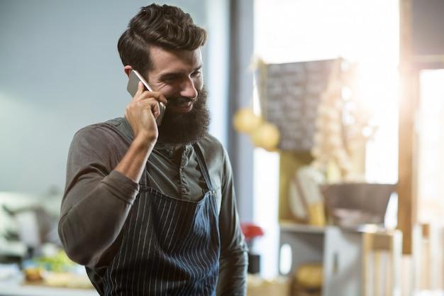 Vendeur parlant au téléphone mobile au comptoir