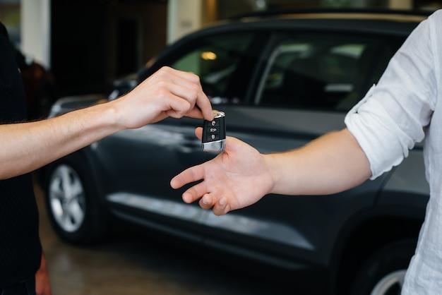 Le vendeur passe les clés d'une voiture neuve à une jeune famille. acheter une nouvelle voiture.