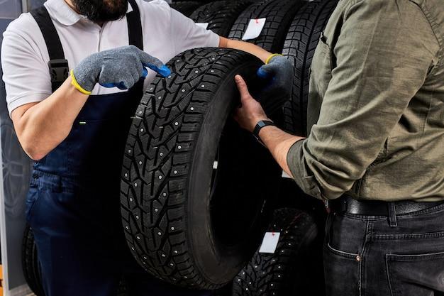 Un vendeur de pneus parlant de la caractéristique du produit au client est venu examiner l'assortiment représenté dans un atelier de service automobile