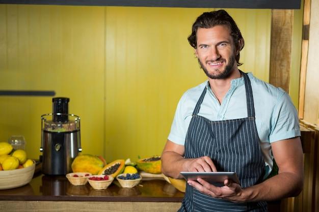 Vendeur souriant à l'aide de tablette numérique