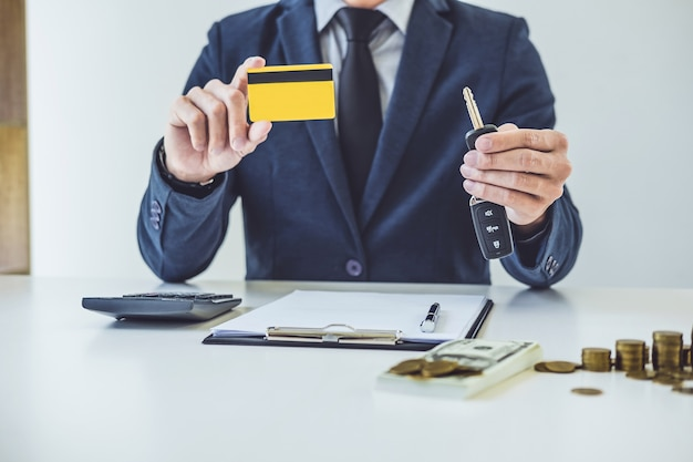 Vendeur tenant une clé, carte de crédit et calcul d'un prix de vente de voiture neuve et à la maison lo