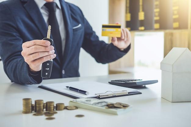 Vendeur tenant une clé, carte de crédit et calculant un prix de vente de voiture neuve