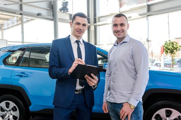 Vendeur travaillant avec le client dans la salle d'exposition, opération d'achat de voiture