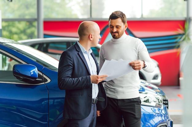 Vendeur vendant des voitures chez un concessionnaire automobile