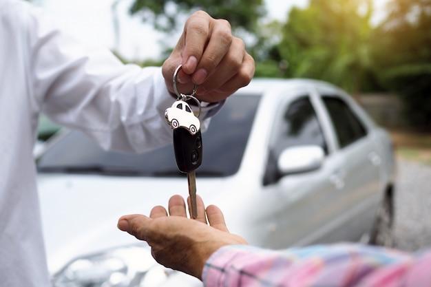 Le vendeur de voiture et la clé du nouveau propriétaire.