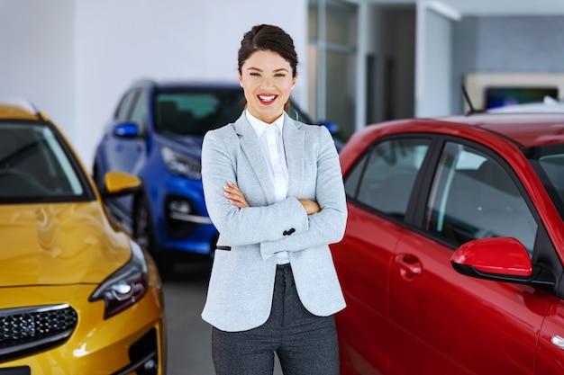 Vendeur de voiture souriant sympathique debout dans un salon de voiture avec les bras croisés et les clients en attente de venir en vente.