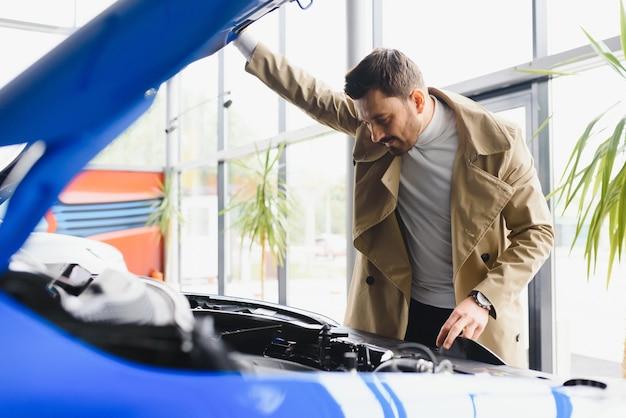 Vendeur de voitures d'âge moyen montrant le moteur au client chez le concessionnaire