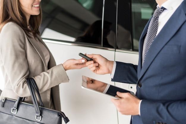 Vendeur de voitures donnant des clés au client