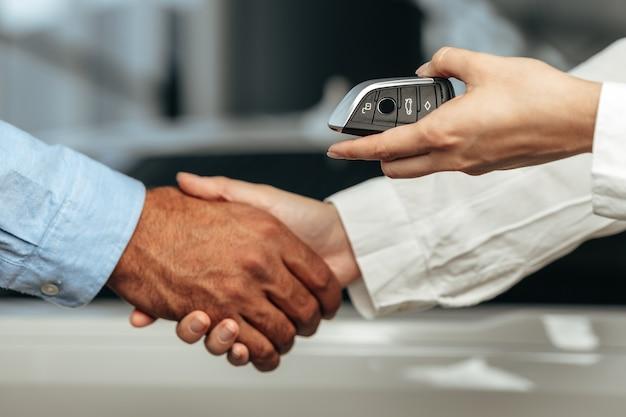 Vendeur de voitures donnant les clés à un client close up