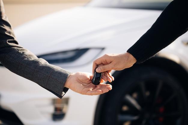 Vendeur de voitures finissant la vente de voiture