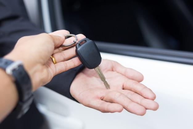 Vendeur de voitures remettant la clé d'une nouvelle voiture à un jeune homme d'affaires devant la voiture blanche