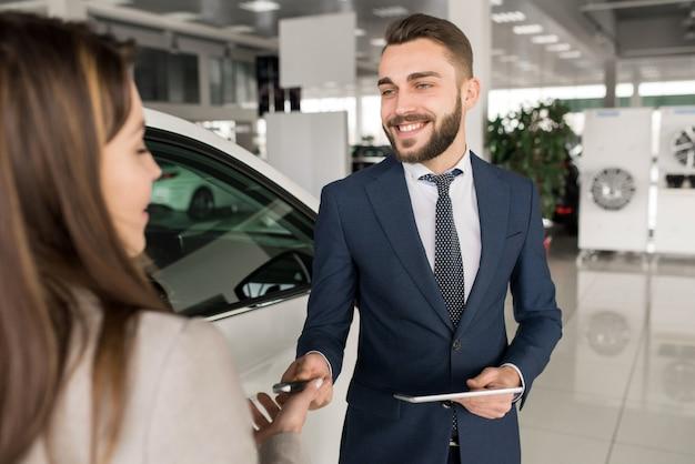 Vendeur de voitures travaillant avec le client