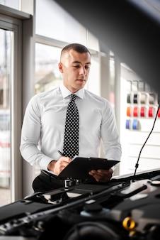 Vendeur vue de face vérifiant une voiture