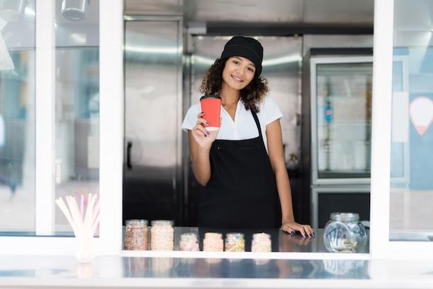 Vendeuse attrayante posant dans un restaurant mobile.