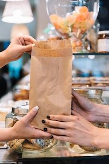 Vendeuse, donnant, croissant, sac