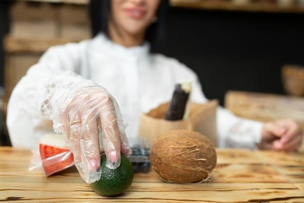 Vendeuse emballe un sac à provisions avec des produits dans un magasin d'aliments naturels.