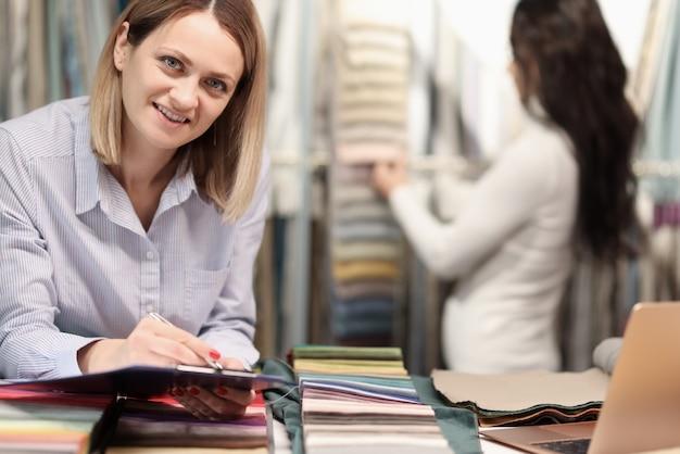 Une vendeuse enregistre la liste des marchandises sélectionnées dans des documents sur le presse-papiers. concept de service client réussi