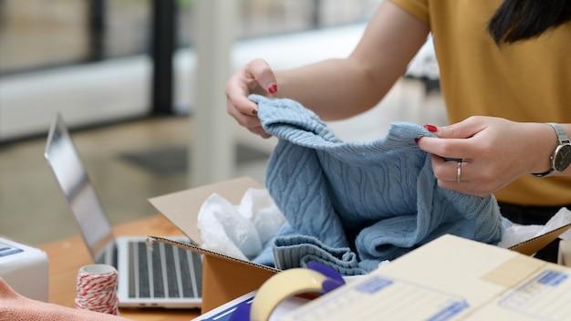 Vendeuse en ligne emballant des pulls dans des boîtes pour la livraison aux clients, vente en ligne, livraison de colis.