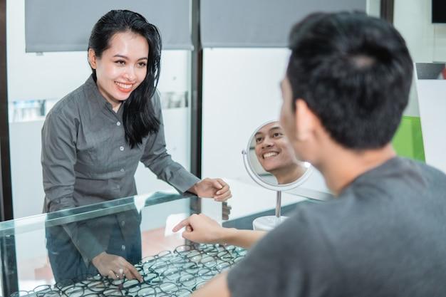 Une vendeuse montre une paire de lunettes dans une fenêtre à un client chez un opticien